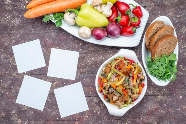 Draufsicht auf frisches gemüse mit pilzen in teller mit brotlaib und gemüse auf braunem, pflanzlichem lebensmittelpilz