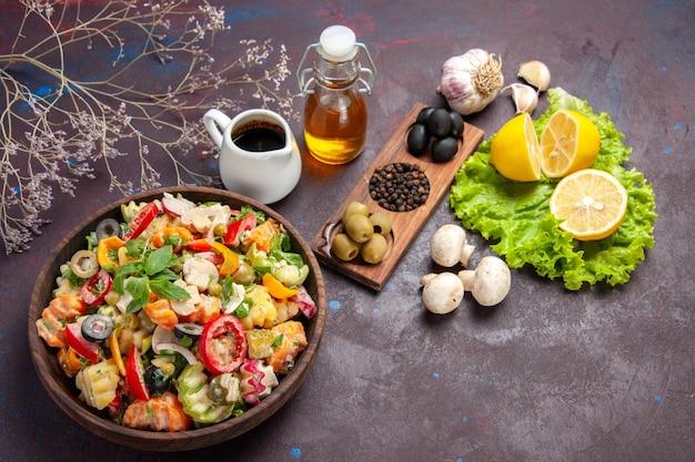 Draufsicht auf frisches gemüse. salat mit oliven und zitronenscheiben auf schwarzem boden essen salat diät snack gesundheit
