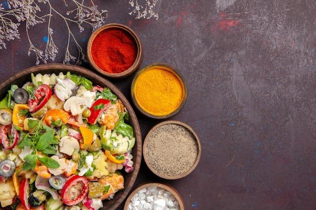 Draufsicht auf frisches gemüse. salat mit verschiedenen gewürzen auf schwarz