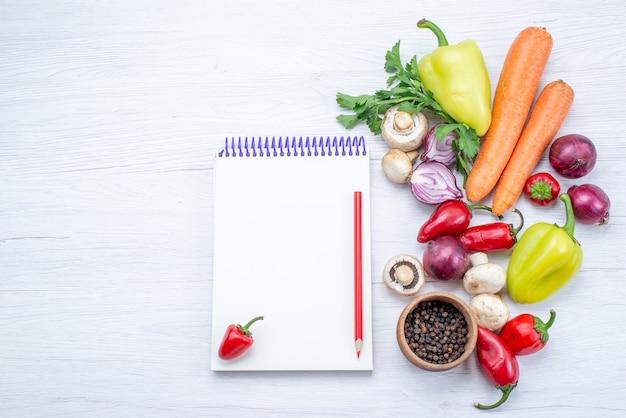 Draufsicht auf frisches gemüse wie pfeffer-karotten-zwiebeln auf leichtem schreibtisch, gemüsemahlzeit-vitamin