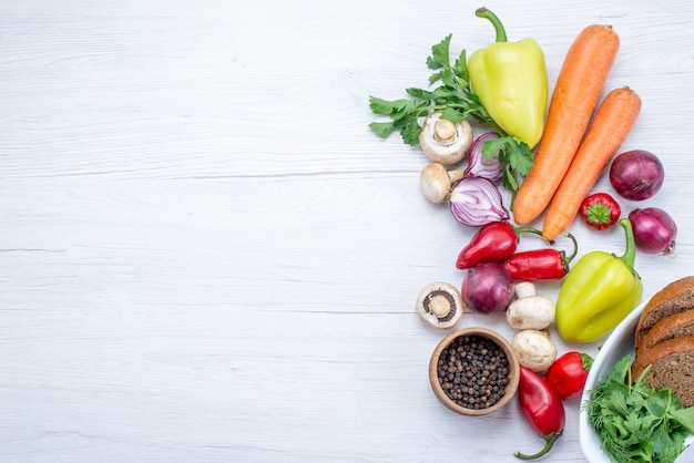 Draufsicht auf frisches gemüse wie pfeffer-karotten-zwiebeln mit brot auf hellem schreibtisch, gemüsemahlzeit-vitamin