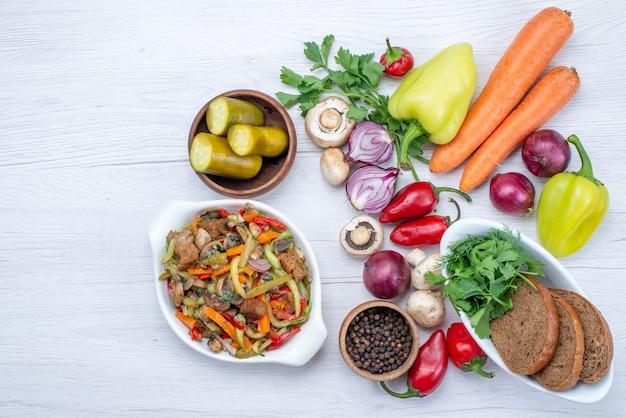 Draufsicht auf frisches gemüse wie pfeffer-karotten-zwiebeln mit brotlaib und geschnittenem fleischgericht auf leichtem schreibtisch, gemüsemahlzeit-vitamin