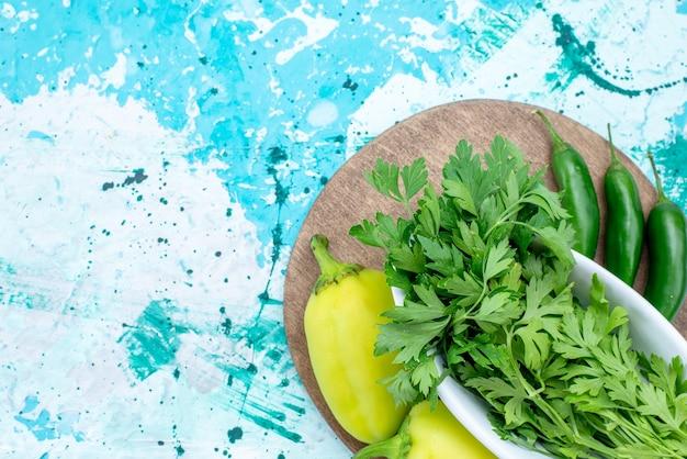 Draufsicht auf frisches grün, das auf der innenplatte zusammen mit grünen paprikaschoten und würzigen paprikaschoten auf hellblau isoliert ist