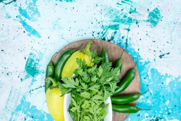 Draufsicht auf frisches grün, das innerhalb der platte zusammen mit grünen paprikaschoten und würzigen paprikaschoten auf hellblauem, grünem blattproduktnahrungsmittelgemüse isoliert wird