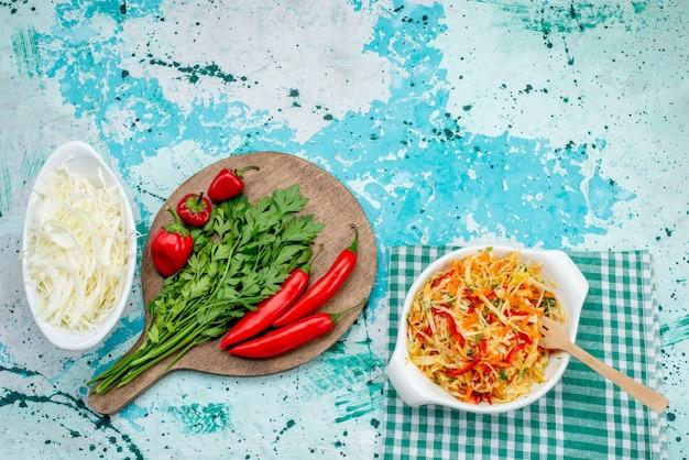 Draufsicht auf frisches grün zusammen mit rotem würzigem paprikasalatkohl auf hellblauer, pflanzlicher grüner nahrungsmittelzutat