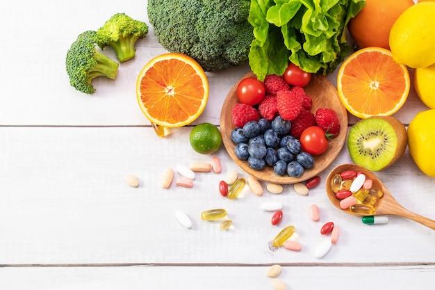 Draufsicht auf frisches obst und gemüse mit unterschiedlicher medizin auf einem holzlöffel