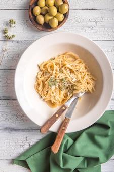 Draufsicht auf frischkäse, oliven, fettucini alfredo nudeln.