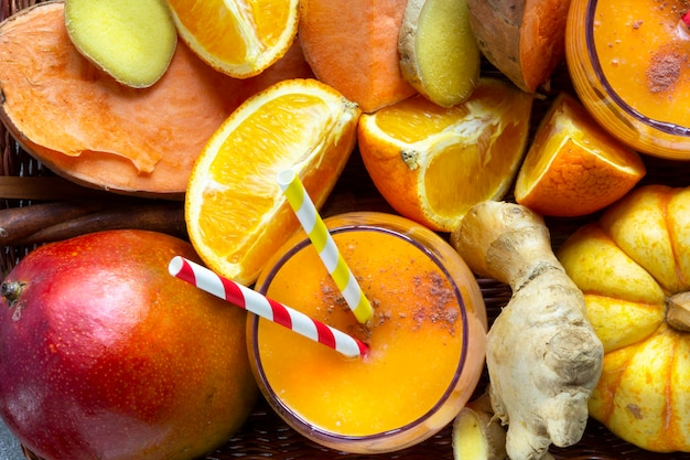 Draufsicht auf frucht smoothie coctail mit orangenfrüchten - süßkartoffel, orange, mango, kürbis, ingwer. veganes, gesundes lebensmittelkonzept. flach liegen