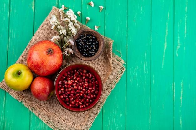 Draufsicht auf früchte als granatapfel- und schwarzdornbeeren in schalen mit blumen, äpfeln und granatapfel auf sackleinen und grüner oberfläche mit kopierraum