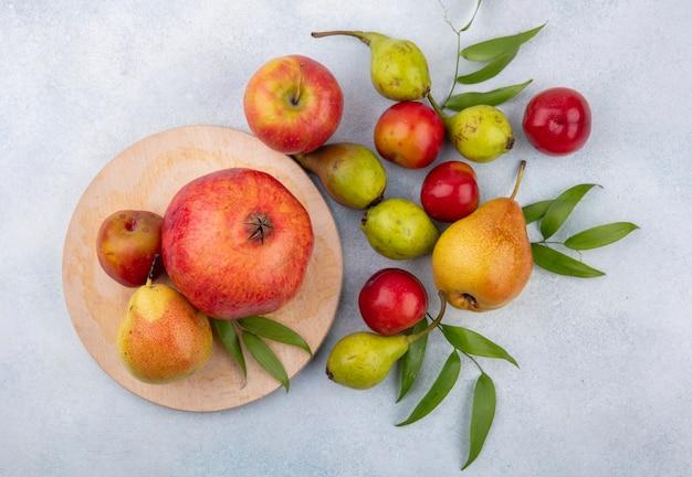 Draufsicht auf früchte als pflaumenpfirsich und granatapfel auf schneidebrett und mit apfel auf weißer oberfläche