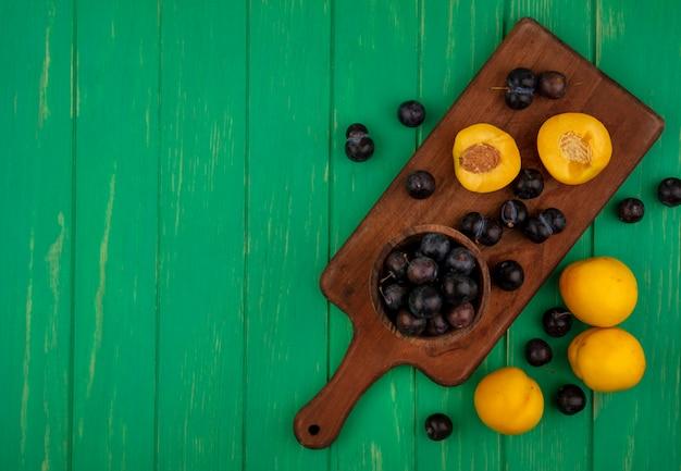 Draufsicht auf früchte als schlehenbeeren in schüssel und halb geschnittene aprikose auf schneidebrett mit ganzen auf grünem hintergrund mit kopienraum