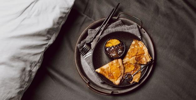 Draufsicht auf frühstücks-crepes mit marmelade auf dem bett