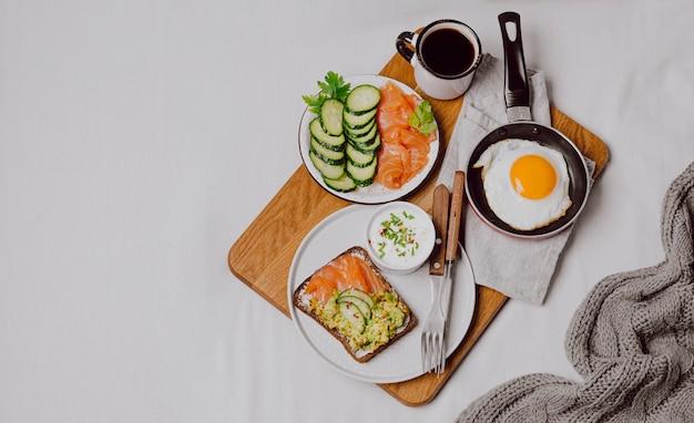 Draufsicht auf frühstücksbrötchen auf bett mit spiegelei und kopierraum