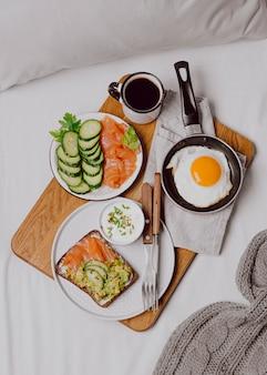 Draufsicht auf frühstücksbrötchen auf dem bett mit toast und spiegelei