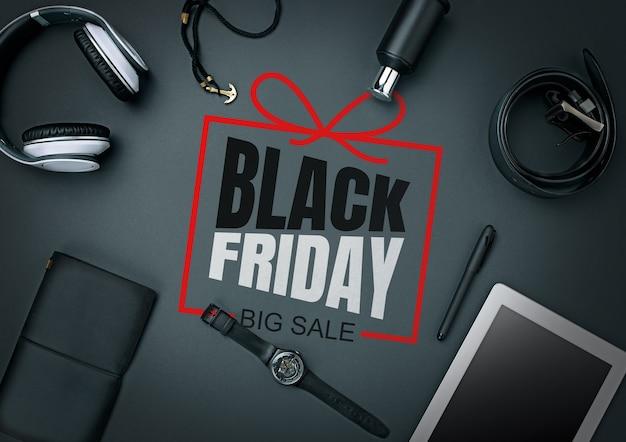 Draufsicht auf gadgets mit schwarzem freitag-schriftzug auf schwarzem hintergrund. copyspace für ihre anzeige. schwarzer freitag, verkauf, finanzen, werbung, geld, finanzen, kaufkonzept. kopfhörer, uhr, tablet.