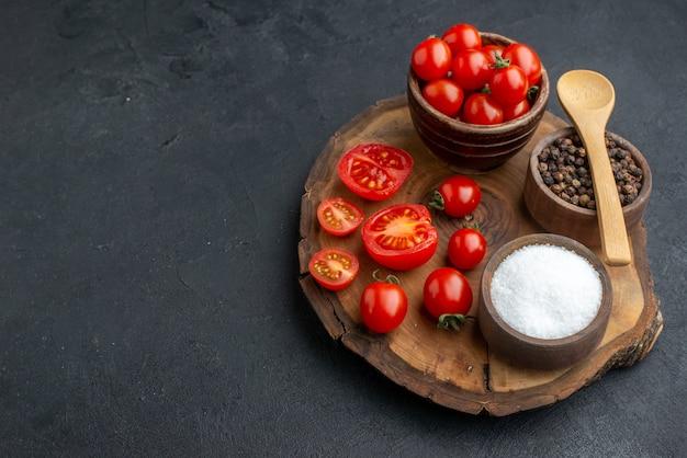 Draufsicht auf ganz geschnittene frische tomaten und gewürze auf holzbrett auf der linken seite auf schwarzer oberfläche