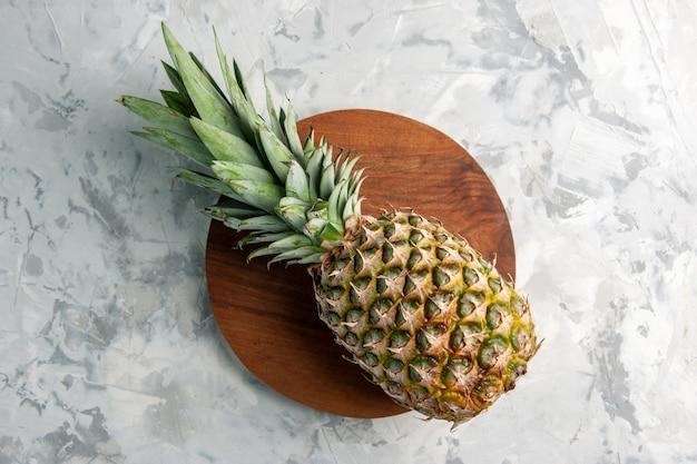 Draufsicht auf ganze frische goldene ananas auf schneidebrett auf marmoroberfläche