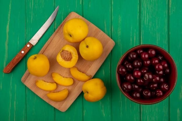Draufsicht auf ganze geschnittene und geschnittene aprikosen mit messer auf schneidebrett mit schüssel kirschen und messer auf grünem hintergrund
