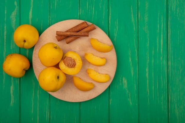 Draufsicht auf ganze geschnittene und geschnittene aprikosen mit zimt auf schneidebrett auf grünem hintergrund mit kopienraum