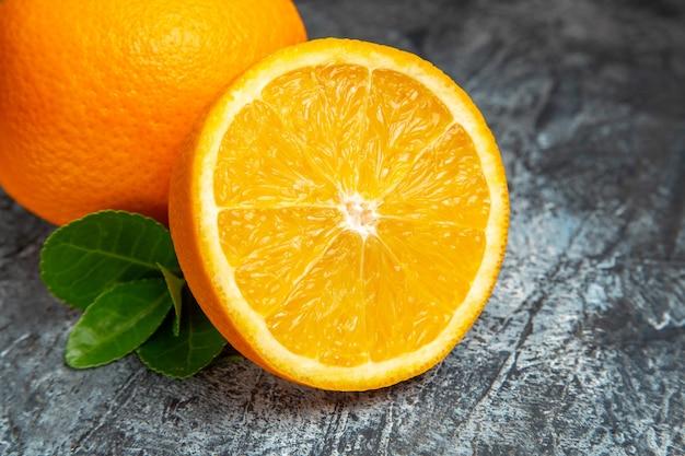 Draufsicht auf ganze und halbierte frische orangen auf der rechten seite des grauen hintergrunds