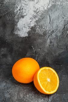 Draufsicht auf ganze und halbierte frische orangen auf grauem hintergrund