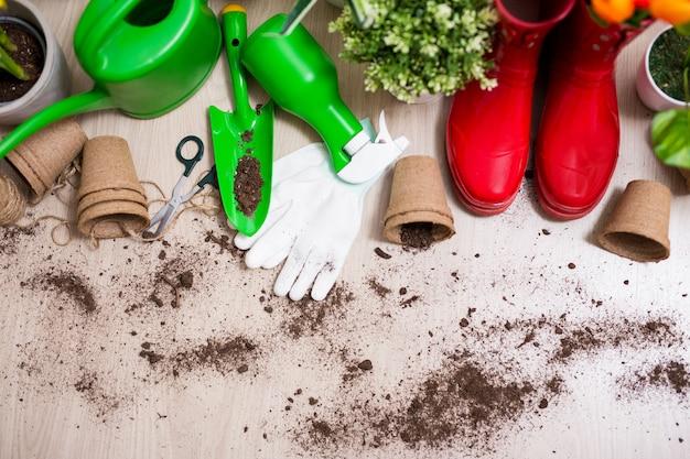 Draufsicht auf gartengeräte und topfpflanzen auf holztischhintergrund