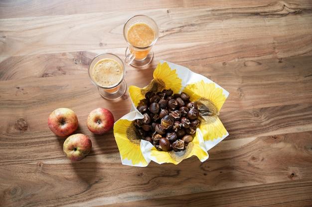 Draufsicht auf gebackene kastanien in einem korb neben frischen äpfeln und heißem apfelwein auf holzschreibtisch.