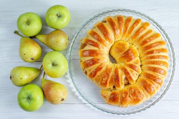 Draufsicht auf gebackenen köstlichen gebäckarmreif gebildet innerhalb glasplatte zusammen mit äpfeln und birnen auf weißem, gebäckkeks süßem auflauf
