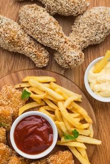 Draufsicht auf gebratene hähnchenschenkel mit pommes frites und soße