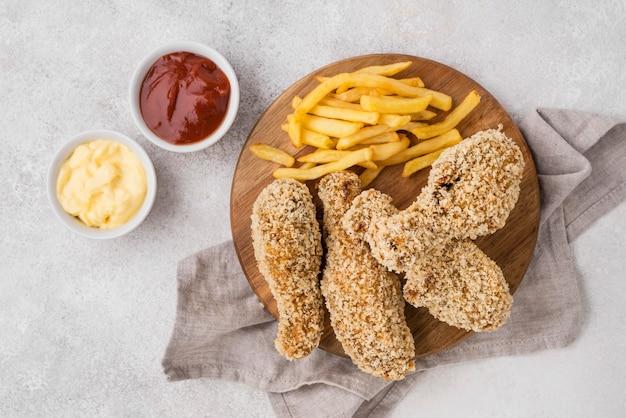 Draufsicht auf gebratene hähnchenschenkel mit saucen und pommes frites