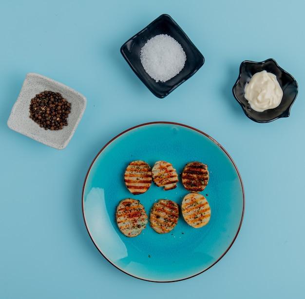 Draufsicht auf gebratene kartoffelscheiben in platte mit schwarzem pfeffersalz und mayonnaise auf blauer oberfläche