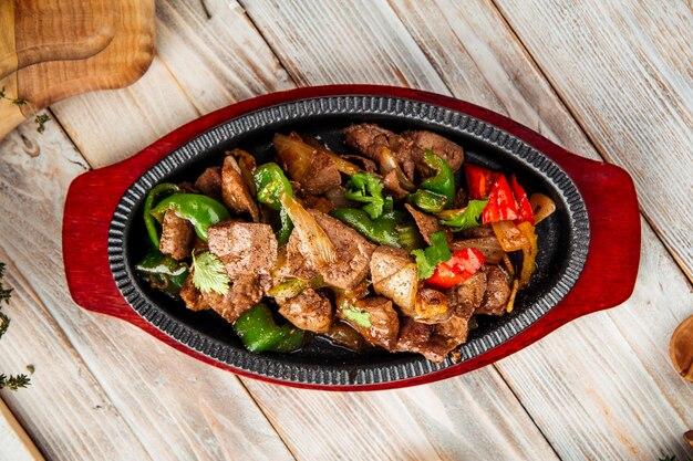 Draufsicht auf gebratenes fleisch mit gemüse in der gusseisenpfanne auf dem holztisch