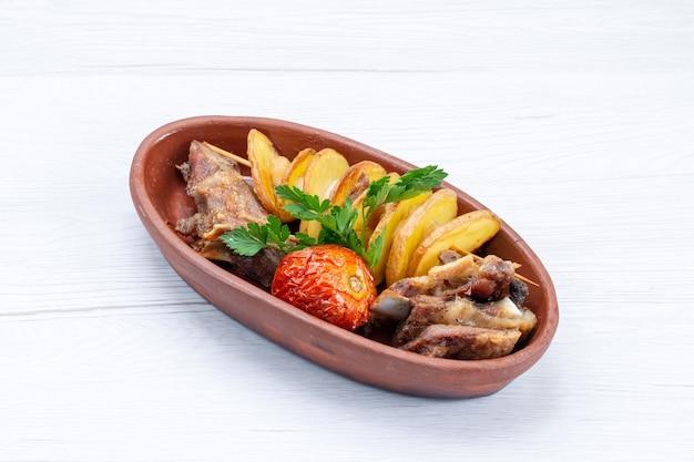 Draufsicht auf gebratenes fleisch mit gemüse und gebackenen pflaumen innerhalb der braunen platte auf weißem, fleischmahlzeit-abendessen-gemüsemahlzeit