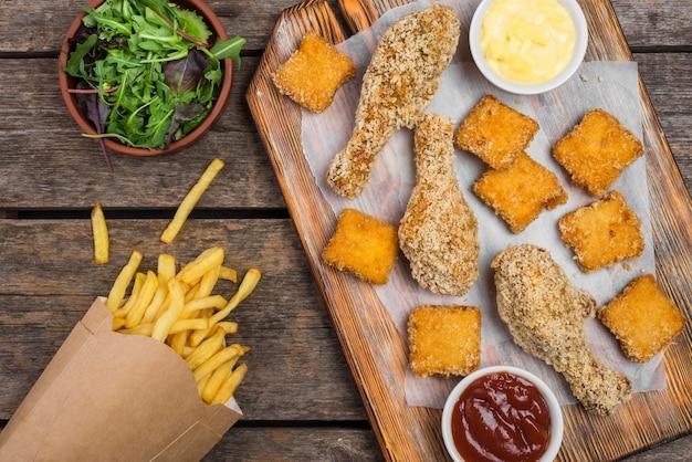 Draufsicht auf gebratenes huhn mit salat und pommes frites