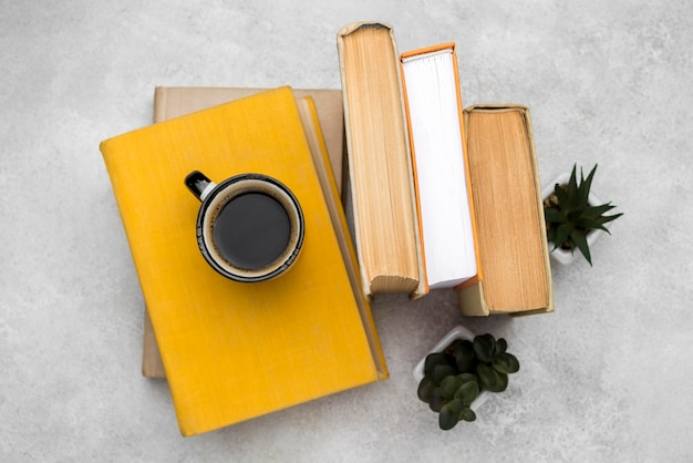 Draufsicht auf gebundene bücher auf schreibtisch mit kaffee und sukkulenten