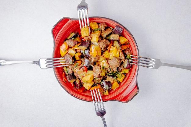 Draufsicht auf gedünstete fleischkartoffeln und auberginen auf dem tisch