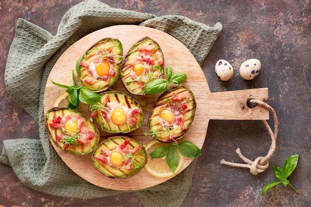 Draufsicht auf gegrillte avocado-boote mit speck- und wachteleiern