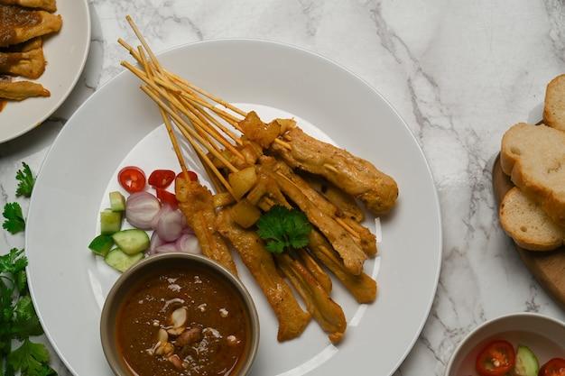 Draufsicht auf gegrillten schweinefleischsatay (moo satay), serviert mit erdnusssauce und gegrilltem brot auf marmortisch