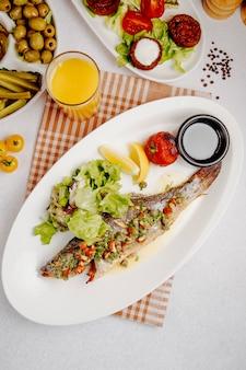 Draufsicht auf gegrillten seebarsch mit frischem salat