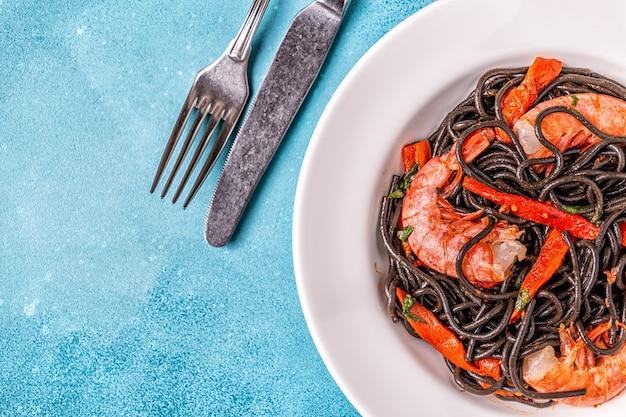 Draufsicht auf gekochte schwarze nudeln mit garnelen