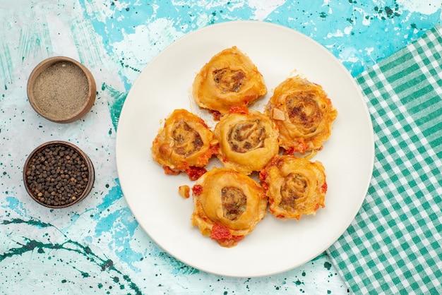 Draufsicht auf gekochte teigmahlzeit mit hackfleisch innerhalb platte mit gewürzen auf hellblauem schreibtisch, teigmahlzeitnahrungsmittelfleischkalorie