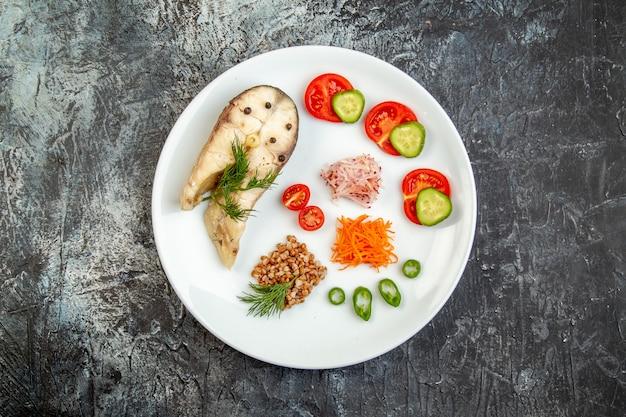 Draufsicht auf gekochten fischbuchweizen serviert mit gemüse grün auf einem weißen teller auf eisoberfläche