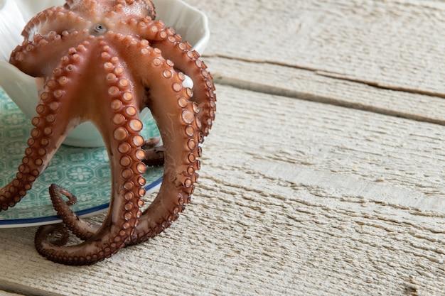 Draufsicht auf gekochten tintenfisch auf rustikalem holzhintergrund. typisches mediterranes proteinfutter, platz für text