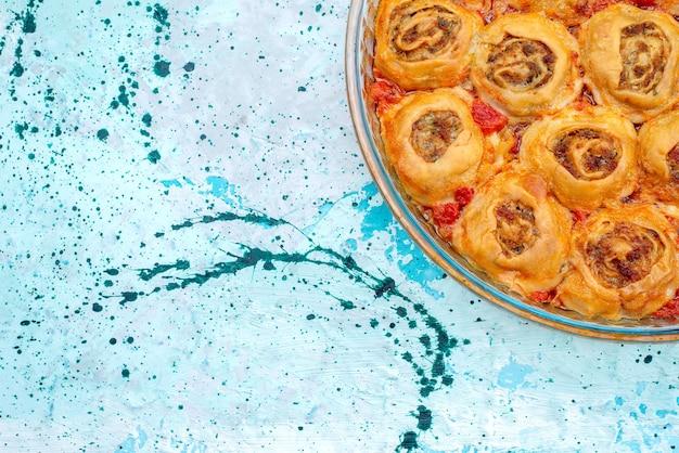 Draufsicht auf gekochtes teigmehl mit hackfleisch und tomatensauce in der glaspfanne auf hellblauem schreibtisch, das backen von fleischteigfarbe kocht