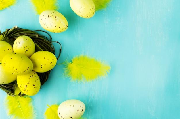Draufsicht auf gelbe ostereier im weidennest und in den gelben federn auf strukturiertem türkisfarbenem hintergrund mit nachrichtenraum.