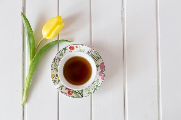 Draufsicht auf gelbe tulpe mit einer tasse tee