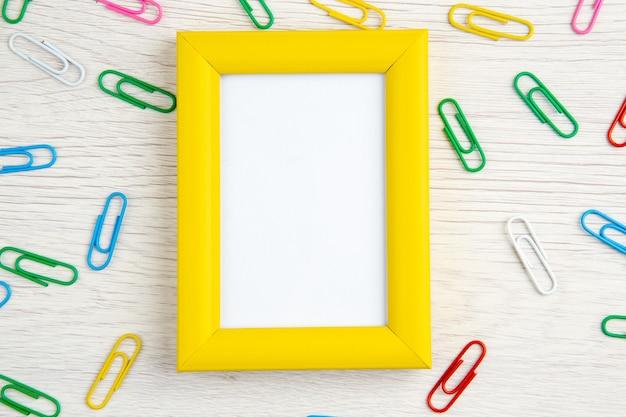 Draufsicht auf gelben leeren bilderrahmen und büroklammern auf weißem holz gestrippt