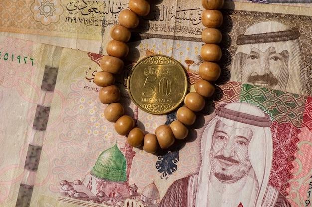 Draufsicht auf geld, banknote und münze von saudi-arabien riyals und gebetskette, im flachen fokus