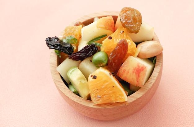 Draufsicht auf gemischte schüssel mit obstsalat. es gibt rosinen, erdnuss, apfel, orange, avocado in holzbecher, verschwommenes licht