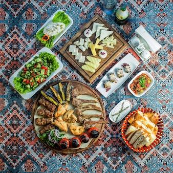 Draufsicht auf gemischten kebab, der mit frischem gemüsesalat-käseteller und auberginenrollen auf einem bunten teppich serviert wird